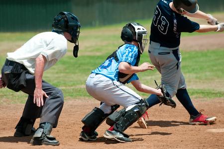 juventud: Recogedor de béisbol con árbitro y bateador durante el juego detrás de la placa. Foto de archivo