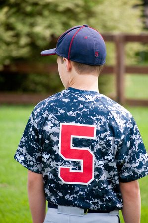 team from behind: Close up of a baseball player outside from behind in a camo jersey looking sideways