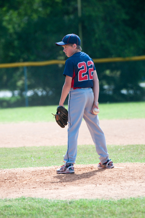 pitching: Youth baseball boy pitching on the mound during a game