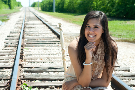 happy seniors: Attractive teen girl sitting on an old chair on railroad tracks.