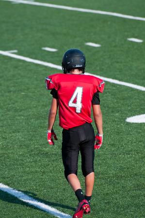 American football teenager on the field looking down. Stock Photo