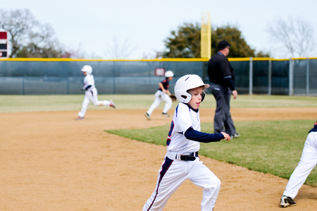 bases: American little league boy wearing helmet running bases during a game while sticking tongue out.