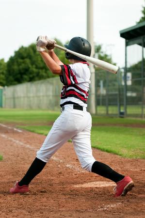 Little League Baseball-Spieler an der Platte, von hinten den Baseballschläger schwingt.