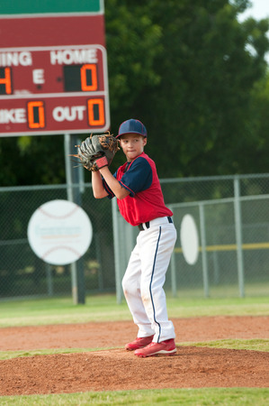 Young little league baseball pitcher about the pitch the ball to batter.