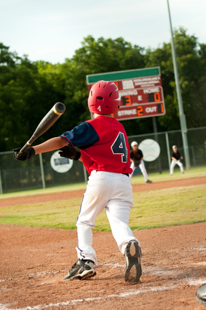 little league: Little league youth baseball player after hitting the ball at bat and ready to run to first base. Stock Photo