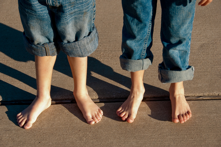 bare feet boys: Two children with bare feet and  pants rolled up standing on sidewalk. Stock Photo