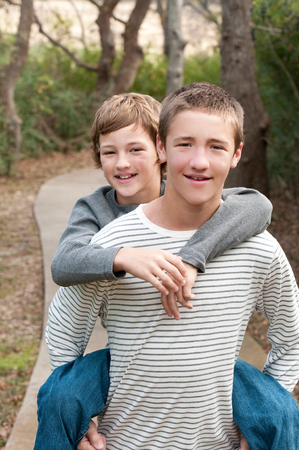 piggy back: Two cute boys that are brothers riding piggy back on sidewalk smiling at camera.