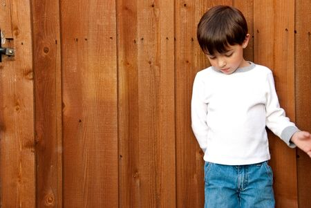 Small cute little boy in jeans looking down next to cedar wood fence