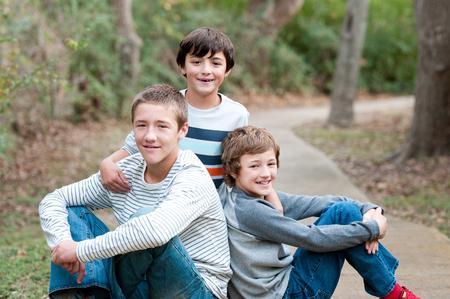 Grupo de tres chicos guapos que son amigos y familia que se sienta en la acera sonriendo a la cámara.