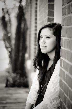 window seal: Close-up of beautiful multiracial latino teen girl sitting in window seal.