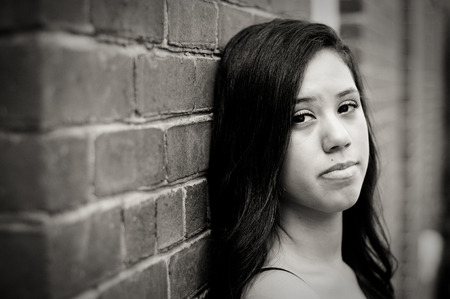 hispanic girl: Portrait of teen graduate in black and white looking depressed and sad. Stock Photo