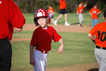 little league: Cute baseball little league player smiling at coach. Stock Photo