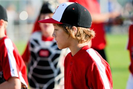 Young baseball player walking back to dugout.