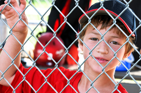 Upclose shot of a Little league baseball player standing in the dugout behind fence.