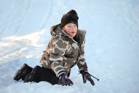 toboggan: Adorable little kid playing in the snow with black ski toboggan and camo jacket.