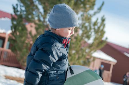 toboggan: Little boy with grey toboggan carrying a sled looking down.