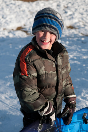 Little boy smiling at camera holding sled.