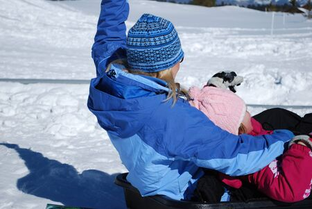 blonde haired: Blonde haired mom in blue ski jacket with young daughter sledding down the snow from behind.