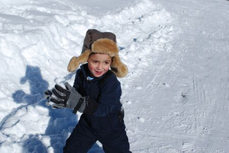 toboggan: Little boy in ski clothes and toboggan playing in the snow ready to have a snowball fight.