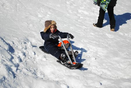 toboggan: Little boy in ski clothes and toboggan playing in the snow sledding on a motorcycle.