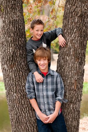 young boys: Portrait of two adorable boys in a tree.