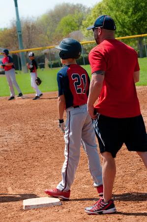 ballplayer: Teen baseball player and baseball coach at first base.