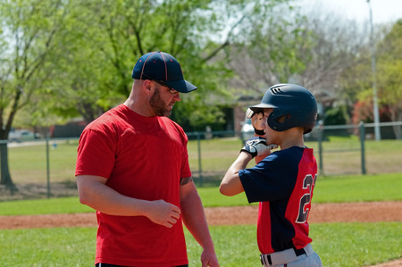 Baseball coach giving instruction to teen baseball boy. Stok Fotoğraf