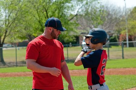 ballplayer: Baseball coach giving instruction to teen baseball boy. Stock Photo