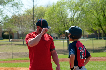 ballplayer: Baseball coach giving signals to teen player