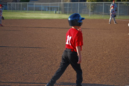 bases: Youth baseball player standing on third base waiting to run the bases. Stock Photo