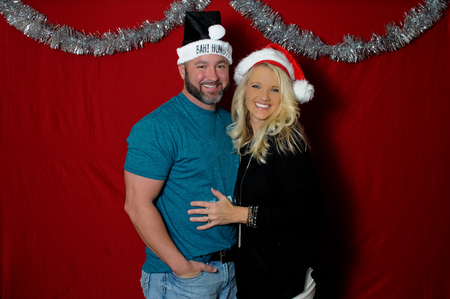 Cute couple in a holiday photo booth wearing santa hats and smiling. Stock Photo