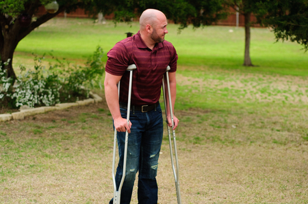 crutch: Muscular bald man on crutches outdoors.
