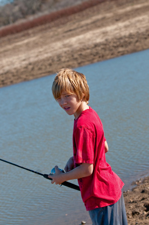 catching: Young boy on a pond catching a fish.