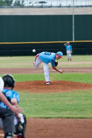 baseball pitcher: Teenage boy on the mound pitching during a game.