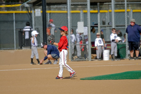 litle: Youth baseball boy walking across the field during a game in red jersey