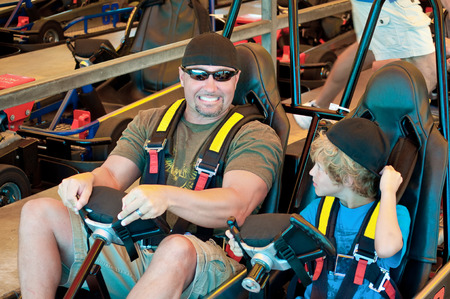 Adorable young kid  with his dad on a go cart at an amusement park.