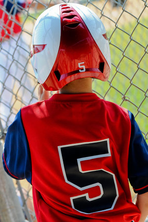 baseball dugout: Youth baseball player in helmet looking through fence of dugout ready to bat.