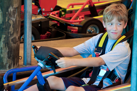 go kart: Adorable young kid on a go cart at an amusement part looking sideways.