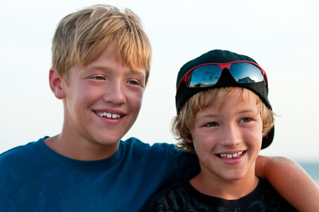 child smile: Close up of two adorable boys not looking at camera outdoors.