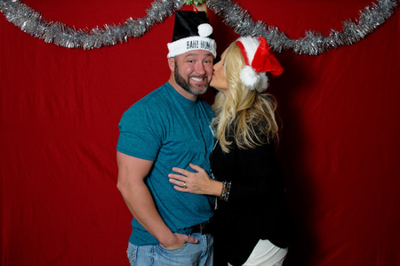 bah: Cute couple in a holiday photo booth wearing santa hats and kissing.