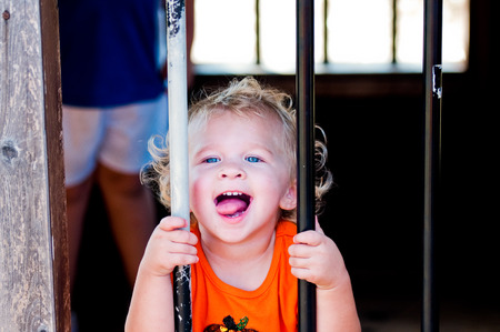 blonde haired: Close up of curly blonde haired toddler girl behind bars at a pumpkin festival. Stock Photo
