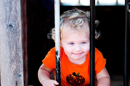 behind bars: Close up of curly blonde haired toddler girl behind bars at a pumpkin festival. Stock Photo