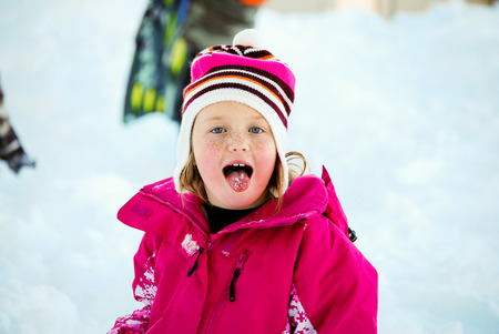 stinking: Portrait of adorable girl with blue eyes wearing a pink coat out in the snow with mouth open and tongue stinking out.