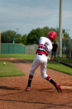 little league: Little league baseball player swinging bat to hit the ball. Stock Photo