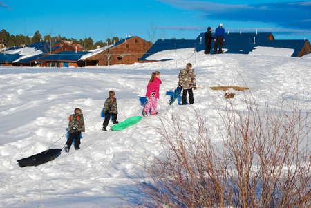 to go sledding: Four kids pulling sleds up a snow hill on vacation.