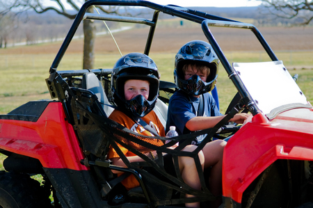 buggy: Happy boy and girl riding a dune buggy out in the country. Stock Photo