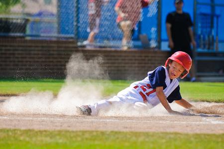 青少年野球選手が自宅でスライディングします。