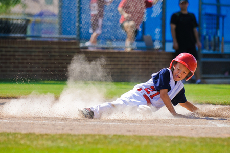 youth sports: Youth baseball player sliding in at home.