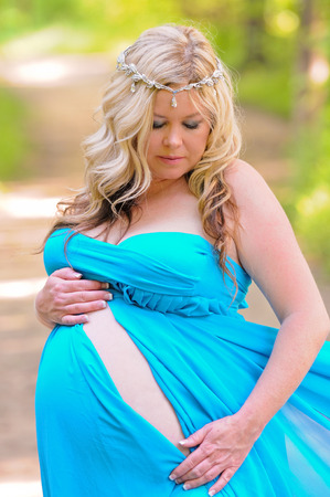 strapless dress: Stunning maternity portrait of beautiful blonde in a blue strapless dress outdoors.
