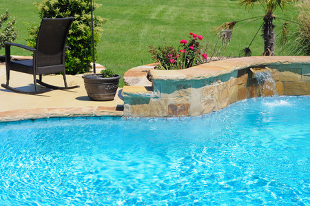 Luxurious swimming pool in backyard of a residential home. Stock Photo